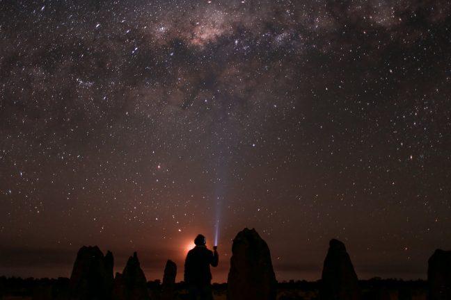 unrecognizable traveler admiring starry sky in nature
